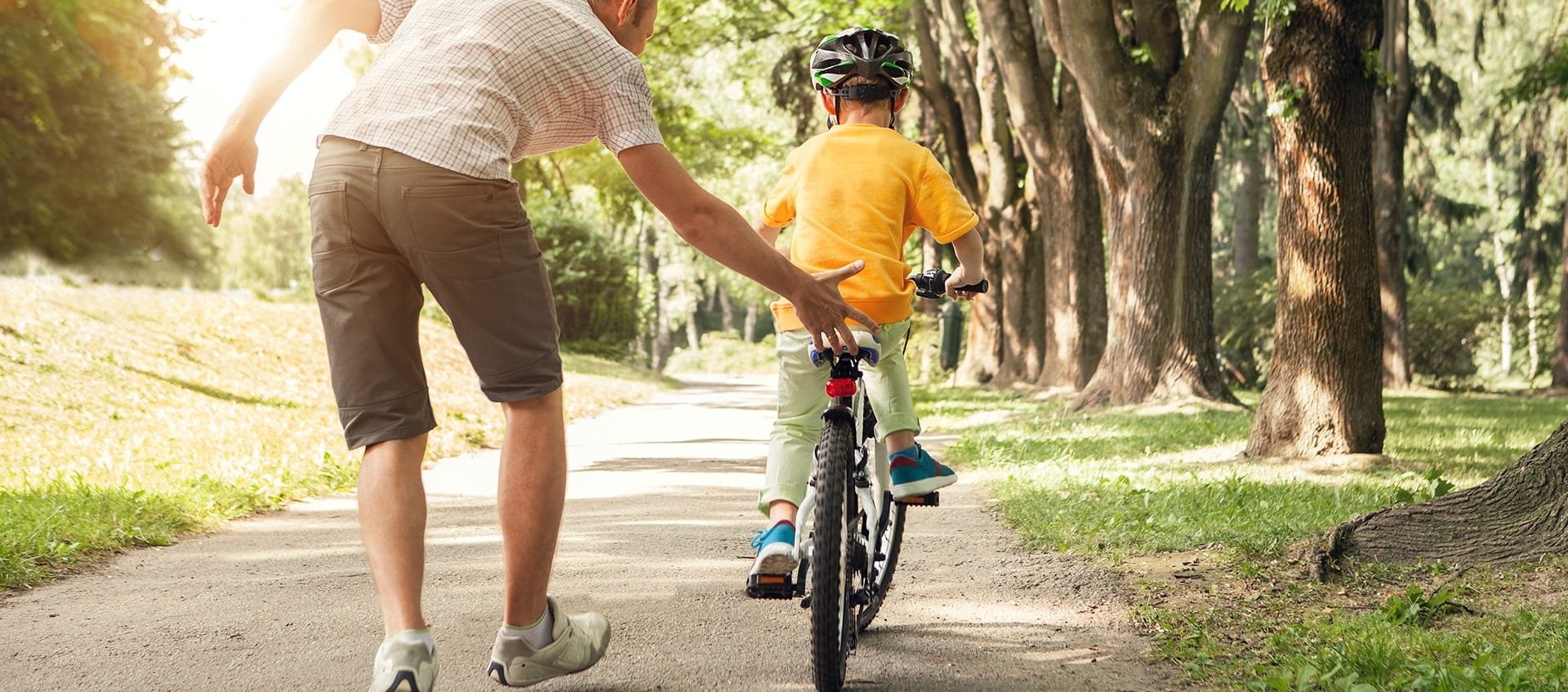 Father on tree-lined sidewalk teaching child to ride a bike