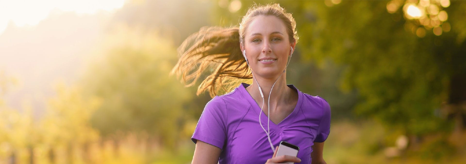 Woman in purple t-shirt jogging with headphones on in Wildcat Ranch
