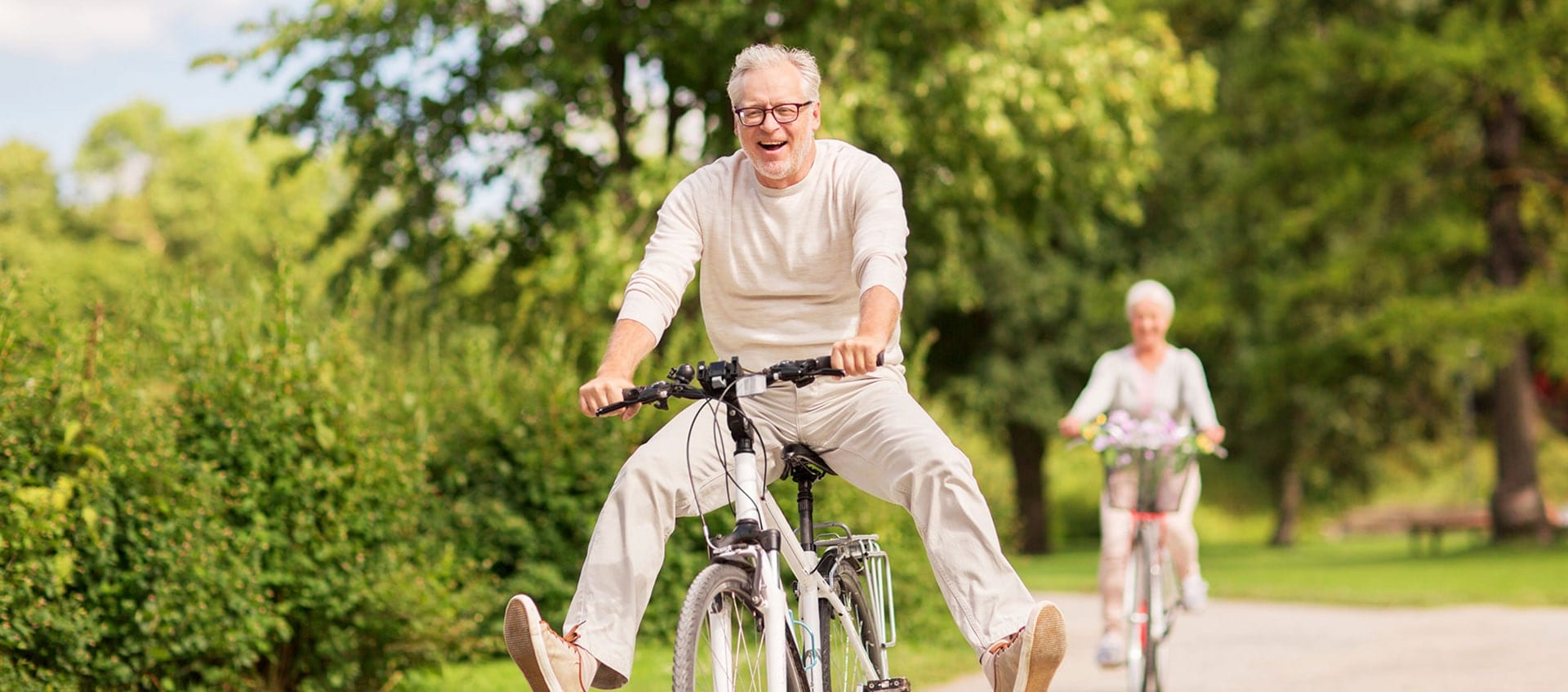 Older Man on a bike laughing with his feet off the pedals and woman riding in distance