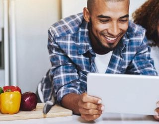 Man and woman smiling and looking at a laptop