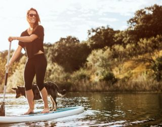 woman and dog paddleboarding on texas lake near wildcat ranch